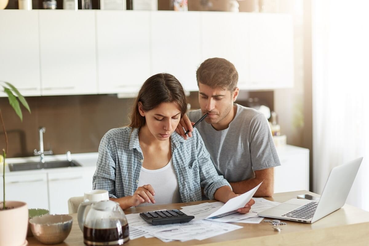 couple looking over investment details at kitchen table